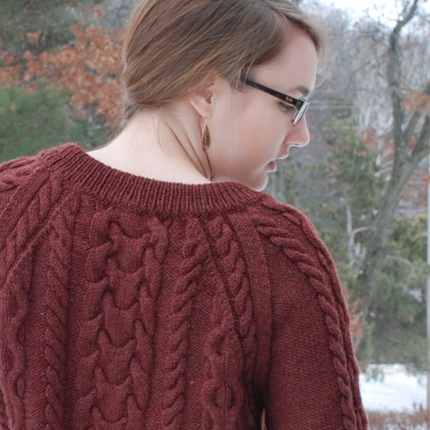 It features a boat neck with shaping to fall lower on the front.